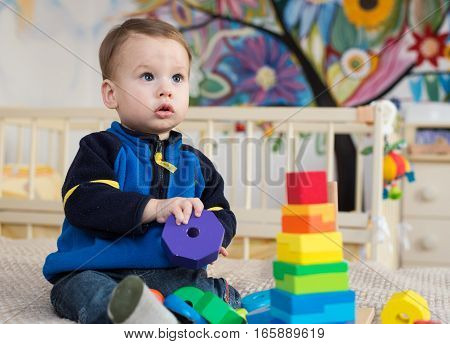 Cute little kid boy playing with lots colorful wooden blocks toy at home.Toddler boy play with toys. Adorable little boy playing with colorful cubes. Happy child playing colorful blocks.