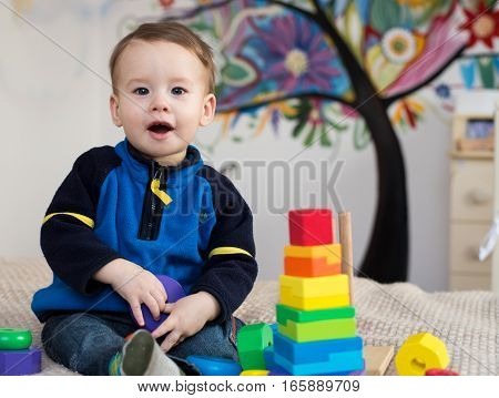 kid opened his mouth in surprise. Cute little kid boy playing with lots colorful wooden blocks toy at home.Toddler boy play with toys. Adorable little boy playing with colorful cubes.