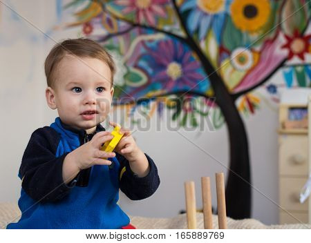 Cute little kid boy playing with colorful wooden blocks toy at home.Toddler boy play with toys. Adorable little boy playing with colorful cubes. Happy child playing colorful blocks.