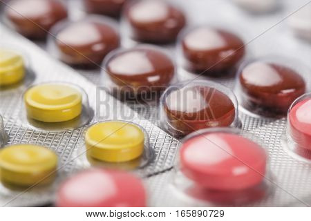 yellow, brown and red pills in a silver plastic packaging