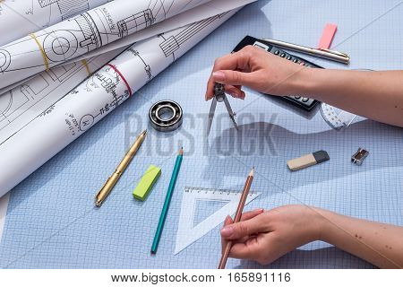 Using engineer compass on graph paper with engineering drawing and tools