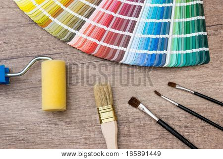 Color chart guide with brush on wooden background