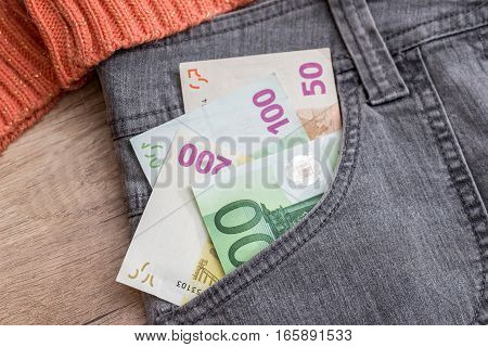 Jeans pocket full of different euro money