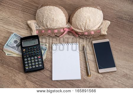 woman's bra with money calculator empty notepad on wooden table