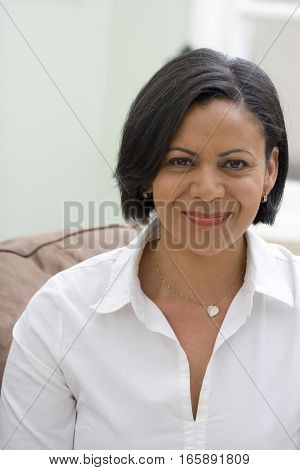 Mature African American woman sitting on her sofa.