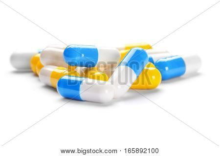 pile of medical pills and blue pills on a white background