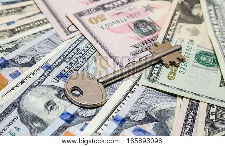 house key above american one hundred dollar bills