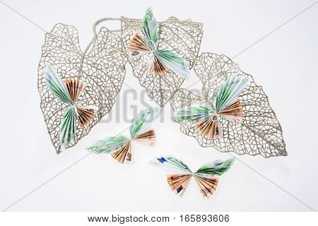 Euro notes in the form of butterflies on decorative glittering leaf