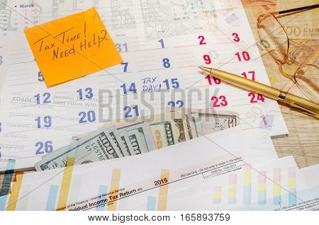 Tax form with calendar pen calculator notepad and glasses