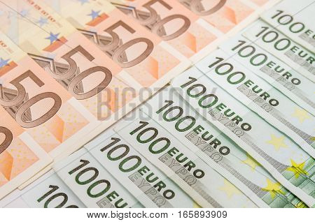50 and 100 euro bills as background
