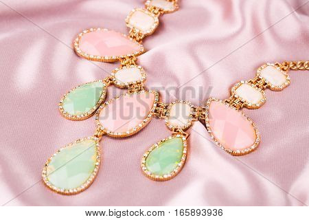 Stylish necklace with colorful stones on pink fabric background.