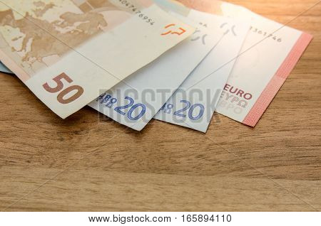different euro banknotes on a wooden table