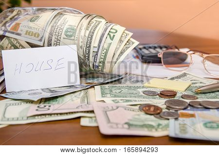 dollar bills in jar with chart and calculator on table