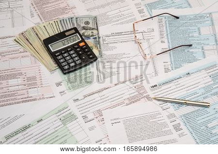 1040 tax form with calculator pen and dollar bills