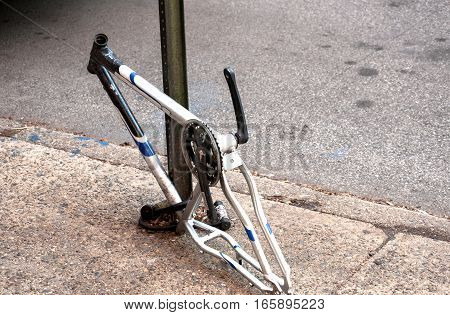 Tied to street pillar bicycle with stolen wheels, fork and seat of which is left only frame