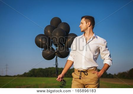 guy in white shirt and brown pants holding black balloons. Standing in field over dark blue sky