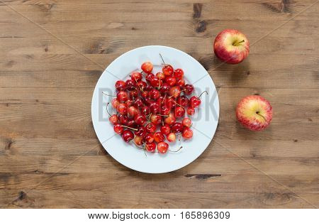 Diet concept. plate of cherries and red apples on wooden table
