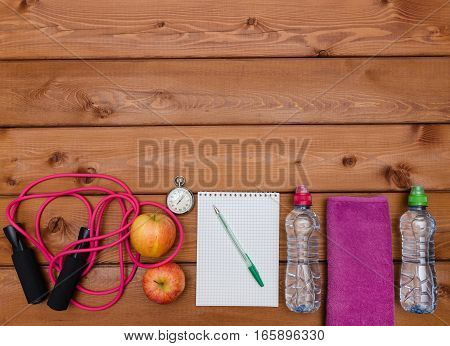 Fitness concept with towel apples bottle of water measure tape notebook and skipping rope on wooden table background