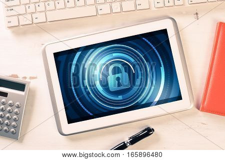Business workplace with office stuff and tablet with padlock icon on screen