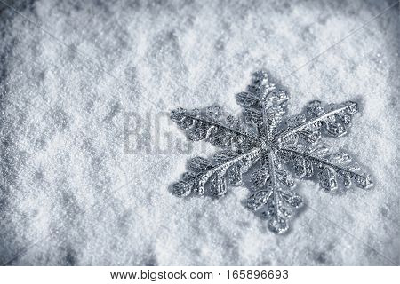 Christmas snowflake on snow background. Christmas decoration. silver toning