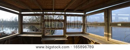 Bird watching hide looking out on to nature reserve water.