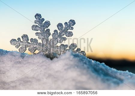 Christmas snowflake in the snow at sunset. Christmas decorations