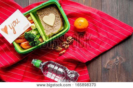 green lunch box for kid on dark wooden background top view mock up