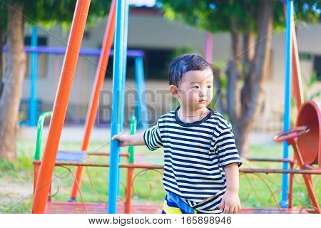 Sad Little Asian Kid At The Playground Under The Sunlight In Summer, Shallow Dof
