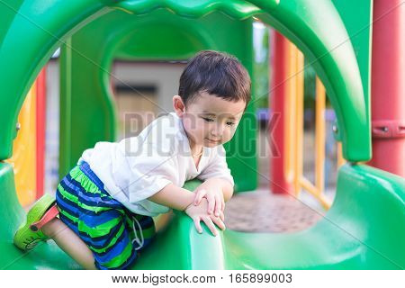 Little Asian Kid Playing Slide At The Playground Under The Sunlight In Summer, Shallow Dof