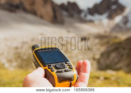 GPS navigator in hand against Dolomites Alps