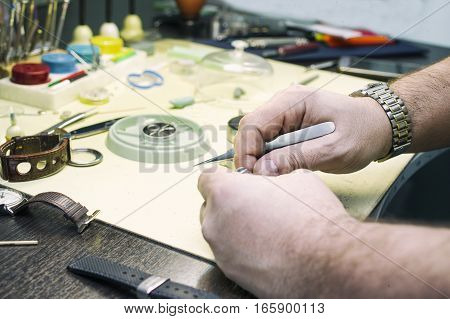 In a clock repair shop. Table with various precise equipment and hands of a service man. Filtered closeup shot