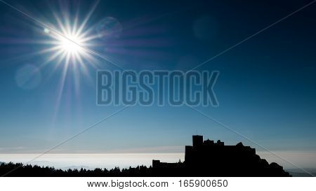 Profile of medieval castle of Loarre on top of hill against bright sun, Huesca, Spain