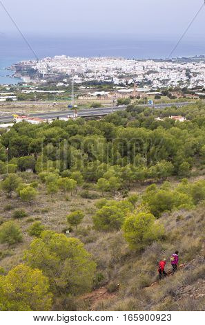 Couple hiking by path over Nerja Caves. Overlooking Town of Nerja Malaga Spain