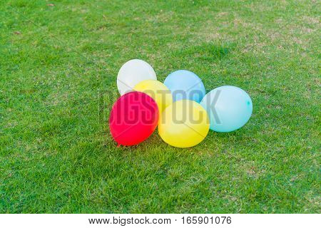 Different Colored Balloons In The Grass.