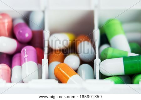 container with various pills in different colors. Focus on a orange pill. soft focus