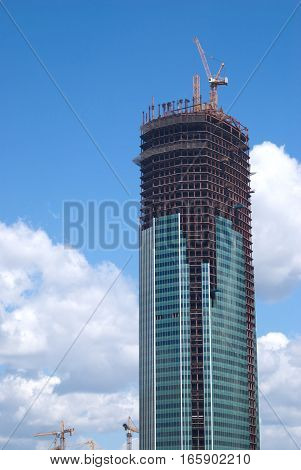 Yellow hoisting tower crane on top of construction skyscraper building vertical view