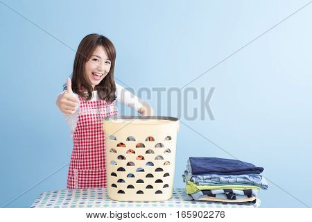 beauty housewife thumb up with ironing and shirt isolated on blue background