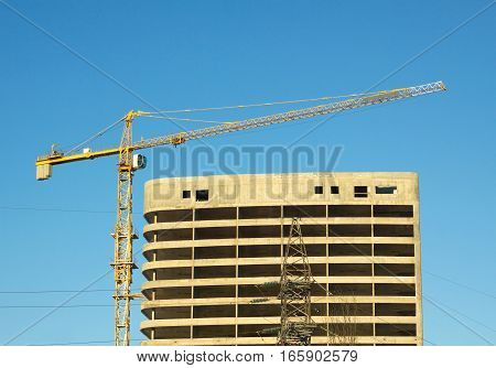 Big yellow hoisting tower crane and top of construction building over cloudless sky