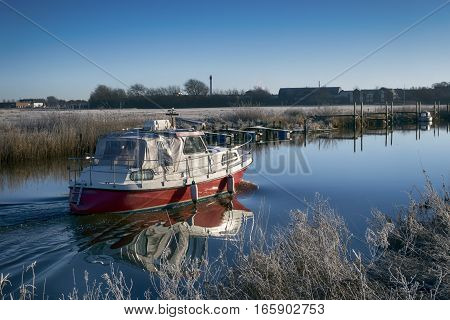 Motorboat sailing on Ribe River in Wadden Sea National Park Denmark.