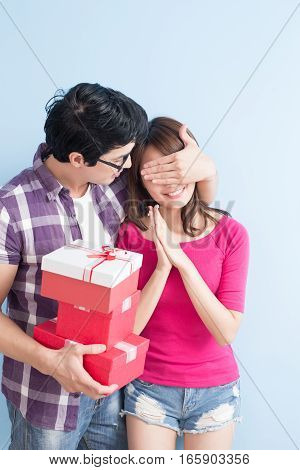 young couple with gift isolated on blue background