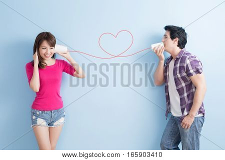 young couple with can phone isolated on blue background