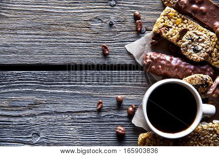 Set of sweets with a cup of coffee. Chocolate bars and granola on a wooden background with milk chocolates. Food candy snack