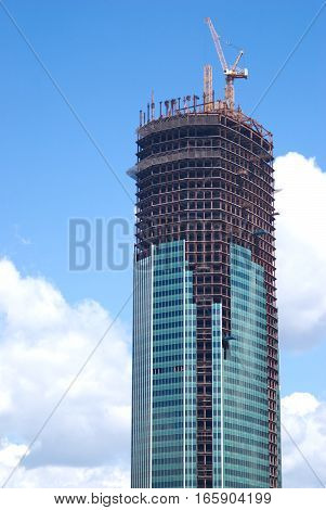 Yellow hoisting tower crane over on top of construction building vertical view