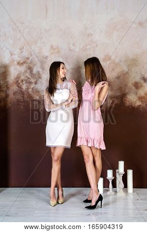Two adult brunette sisters smiling to each other in studio
