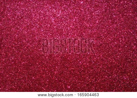 Red glitter paper background. Festive abstract texture