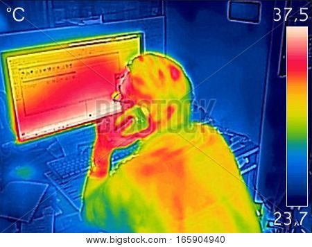 Infrared thermal image showing the heat emission while a man working on a computer and talking on cell phone