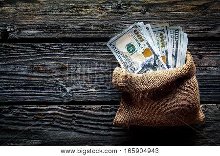 bag full of dollars. Bag full of money hundred dollar bills on wooden background
