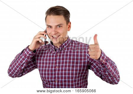 Picture of a smiling young businessman talking on the phone showing thumbs up