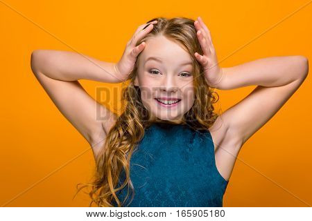 The surprised teen girl with long hair on orange studio background