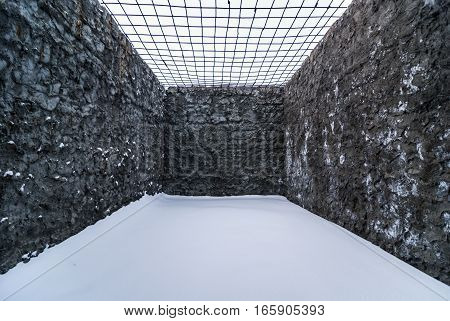 Interior of opened cell for walking in old abandoned prison in Kolyma